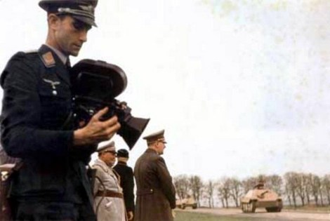 The man holding the film camera is Walter Frentz (21 August 1907 - 6 July 2004), one of Hitler's personal cameraman. from 1939 to 1945, he was closely associated with photographing and filming activities of higher echelons of leaders of Nazi Germany, including Hitler.